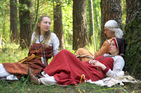 Smolensk, Russia - August 09, 2014, Girls in old Russian national dress sitting in the woods on a halt at the festival of historical reconstruction Gnezdovo Editorial