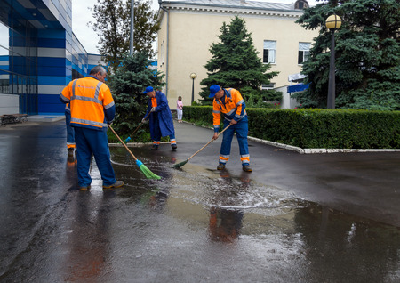 suggests: Simferopol, Russia - June 15, 2016: Janitors disperse brooms puddles after the rain in front of the airport of Simferopol