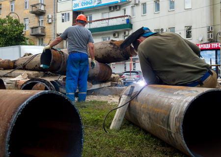 mains: Voronezh, Russia - June 16, 2016: Workers changing mains pipe heat supply in the city of Voronezh Editorial