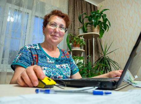 he said: Elderly a smiling woman sitting and working at his laptop
