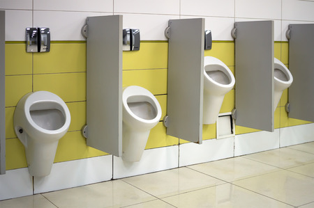 societal: Urinals in a public toilet installed at various heights for high and low people Editorial