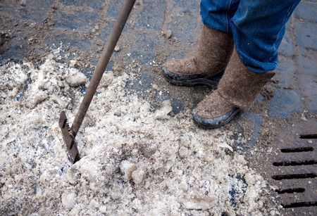 crowbar: Janitor cleans the ice on the street with a crowbar Stock Photo