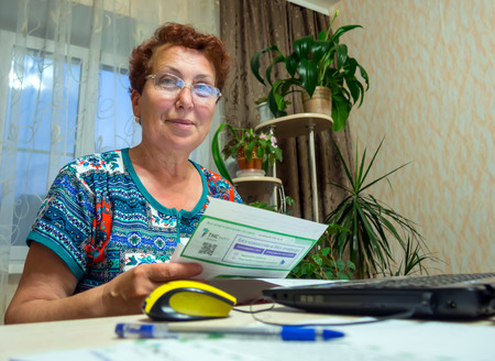 he said: Voronezh, Russia - June 19, 2016: Elderly woman holding a receipt and is going to pay for it in the online bank