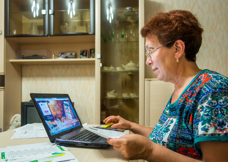 he said: Voronezh, Russia - June 19, 2016: Elderly a smiling woman uses the online system of the bank to pay the bills