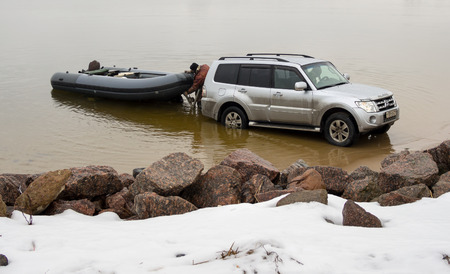 Saint-Petersburg, Russia - March 05, 2016: Man is released from the car Mitsubishi Pajero had brought the boat on the pond Publikacyjne