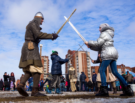 maslenitsa: Sosnovy Bor, Russia - March 13, 2016: Comic battle with swords with the residents of the city as part of the entertainment program Shrovetide festivities