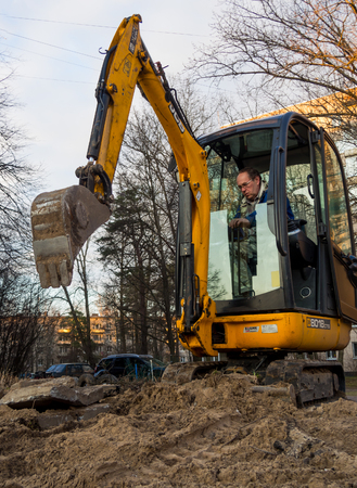 Sosnovy Bor, Russia - April 7, 2016: Mini excavator digging a trench under the city communications