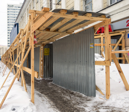 roof profile: Murmansk, Russia - March 14, 2017: Wooden fencing of the footpath during construction