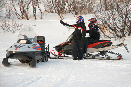 Murmansk, Russia - February 15, 2010: The driver of a snowmobile indicates the way to another friend Stock Photo - 79367113