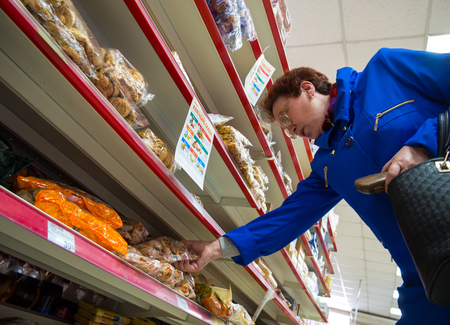 Voronezh, Russia - April 27, 2017: An elderly woman chooses sweets on the shelves of the supermarket Editorial