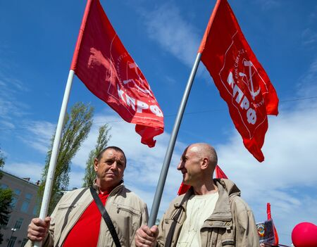Voronezh, Russia - May 01, 2017: Two participants of the May Day demonstration carry the flags of the Communist Party