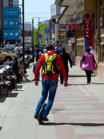 Voronezh, Russia - May 01, 2017: A man is riding on a sidewalk on a monocycle