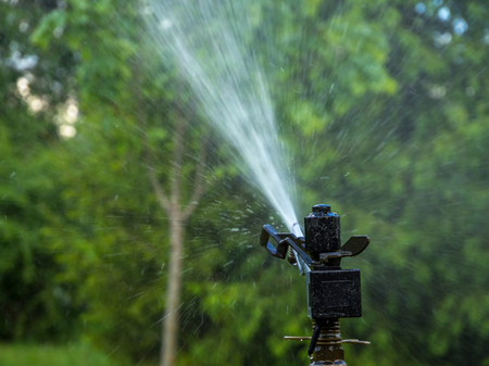 Automatic irrigation system waters the vegetation neighborhood Stock Photo