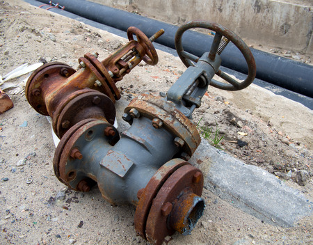 The old dismantled valves of the heating system lie near the trench