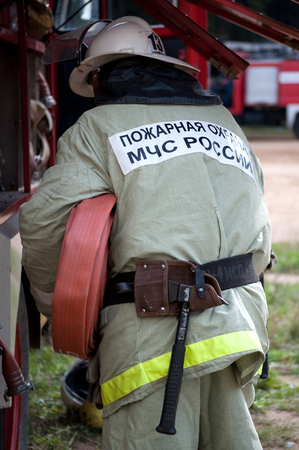 Yartsevo, Russia - August 26, 2011: The fireman pulls out the fire hose from the car 報道画像