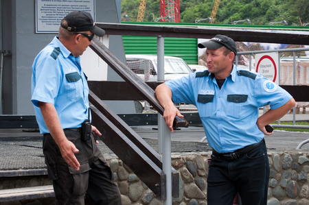 Sochi, Russia - August 05, 2011: The conversation of two guards at the entrance to the Gornaya Karusel ski lift, Sochi