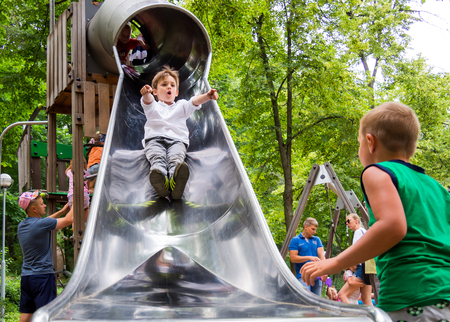 Voronezh, Russia - June 24, 2018: Boys ride on the slide of the playground