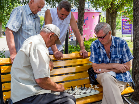 Voronezh, Russia - August 12, 2018: Chess game takes place on a park bench with the participation of spectators