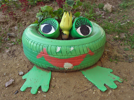 Flower bed in the shape of a frog, made from old tires Stock Photo