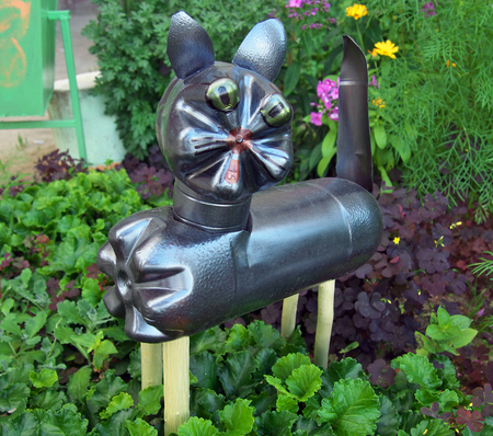 Cat made of used plastic bottles on a flower bed Stock Photo