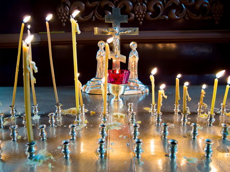Burning candles before the crucifix in the interior of an Orthodox church Stock Photo