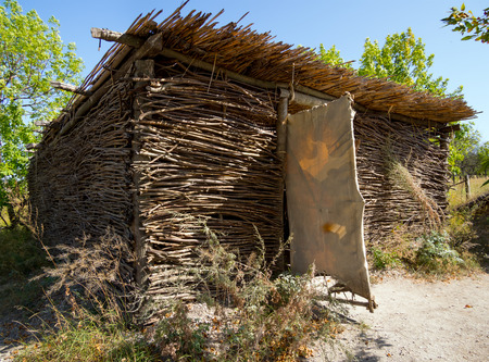 A hut with walls of interlaced twigs, covered with reeds Stock Photo