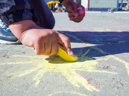 The child draws on the asphalt the sun