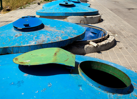 Large stationary trash containers embedded in the ground Stock Photo