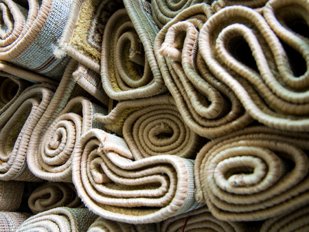 Rolled up carpets are stacked on the rack warehouse Banco de Imagens