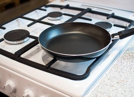 Empty frying pan on a gas stove burner Imagens