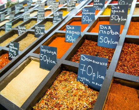 Rows of containers with spices at the grocery market