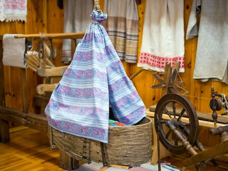 Antique wicker baby cradle in the interior of the hut Imagens