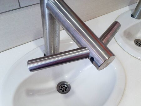 Unusual contactless faucet on the washbasin in the bathroom Imagens