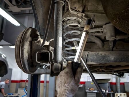 Auto mechanic inspects the undercarriage of a car