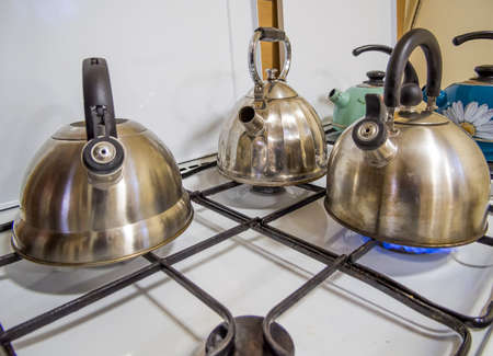 Several kettles are standing on the gas stove of a shared kitchen