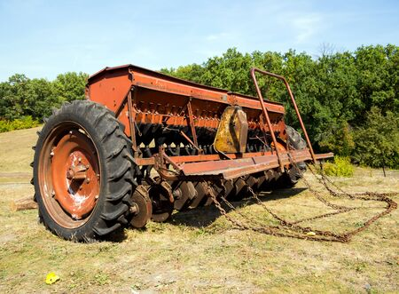 Grain seeder stands on the edge of the field