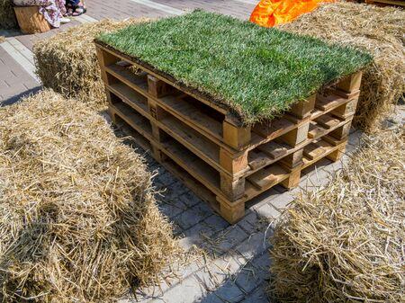 Unusual furniture: table made of Euro pallets, chairs made of straw bales