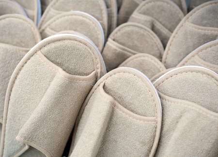 Many beige indoor slippers made of fabric