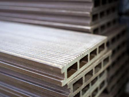 Polymer decking board stacked in a building materials warehouse