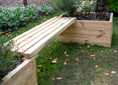 Wooden bench connecting two tall flower beds
