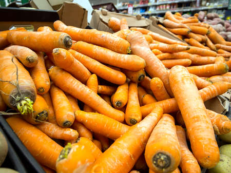 Fresh carrots lie on the counter of the supermarket