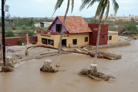 devastation: Damaged by hurricane house with dirty rain water around