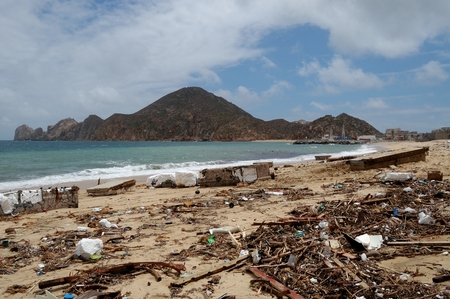 decimated: Trash on the Medano beach Cabo San Lucas and view of mountains Editorial