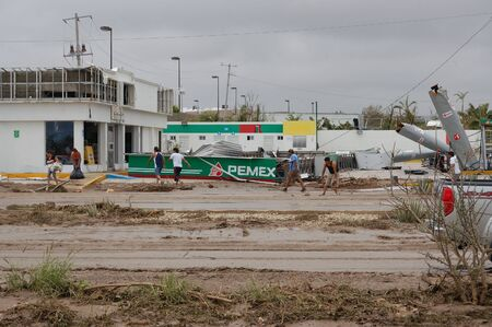 decimated: Track full of dirt in front of Broken by hurricane Odile gazstation Pemex Editorial