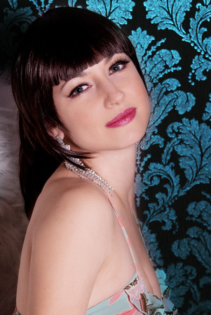 portrait of a young beautiful girl brunette with bangs in the Studio