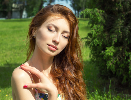 beautiful young girl with red hair big full lips relaxed resting in the Park photo