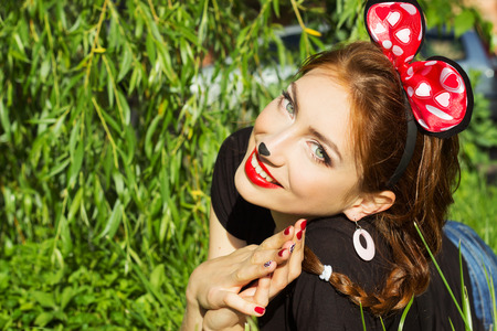 mickey: beautiful girl happy smiling in the costume of a mouse with a big red bow down on the grass in the Park