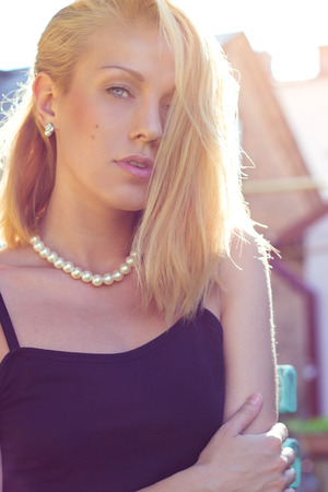 portrait of a beautiful blonde girl with blue eyes against the wall on the streets of the city on a summer day photo