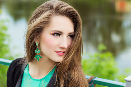 young beautiful sexy girl in a green dress with beautiful makeup with green shackles sitting on the river Bank in the city photo