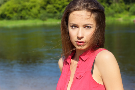 beautiful young sexy girl in the red shirt is standing on the river Bank in Sunny day photo